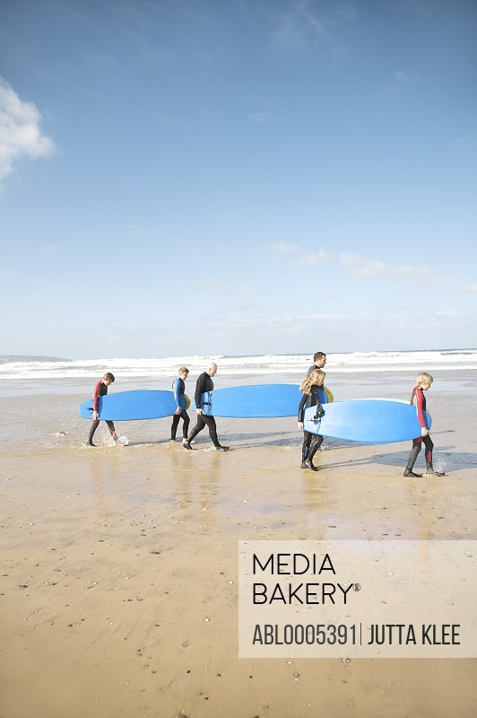 Men and children walking on a beach carrying surfboards