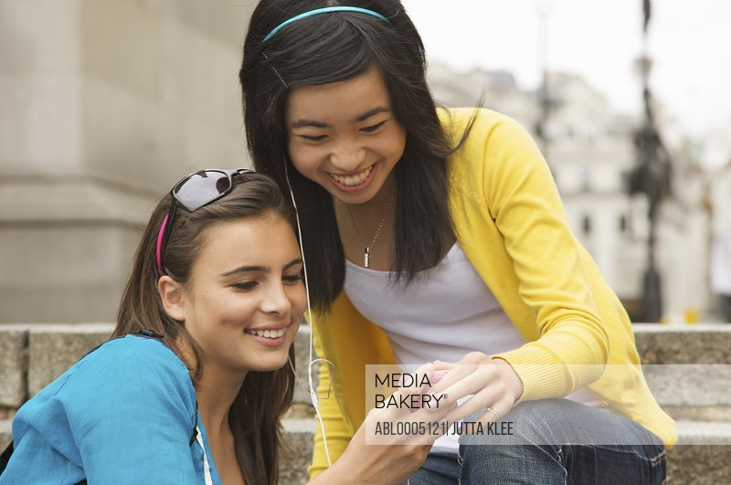 Two smiling teenaged girls sitting on steps holding a mp3 player