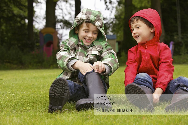 Two Boys Putting on Wellington Boots Outdoors