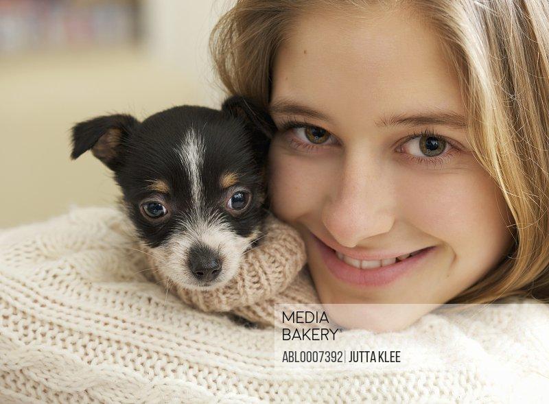 Teenage Girl Hugging Tiny Puppy
