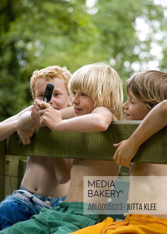 Boys with arms over wooden fence using cell phone