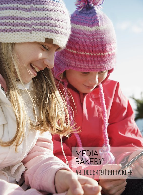 Two young girls wearing woolly hats and holding a mp3 player