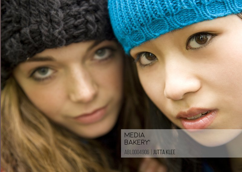 Extreme close up of two teenaged girls wearing woolly hats
