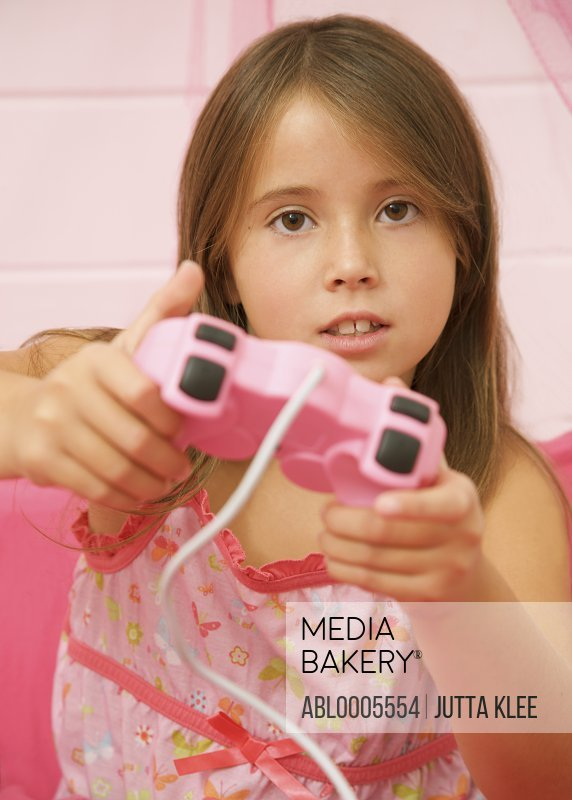 Girl playing and holding a pink game controller