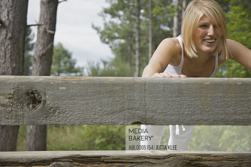 Smiling young woman leaning over a wooden beam doing press-ups