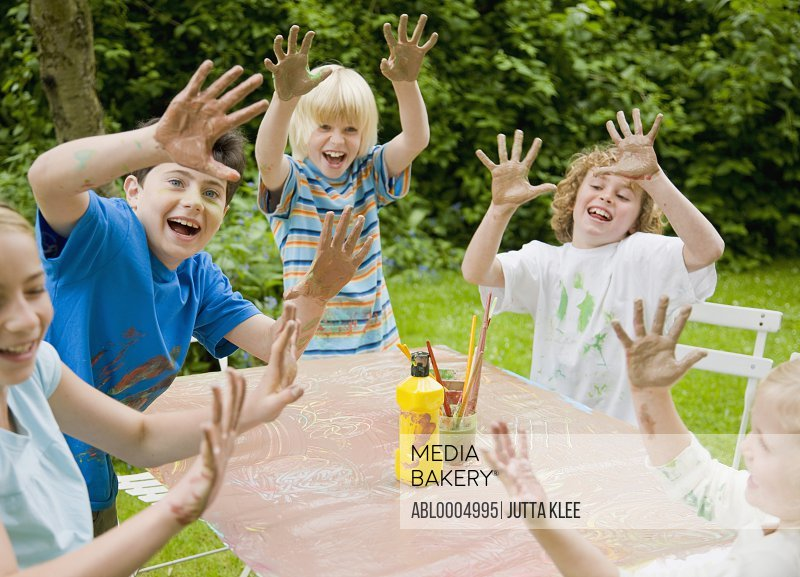 Children smiling and laughing with their arms up and hands covered in paint
