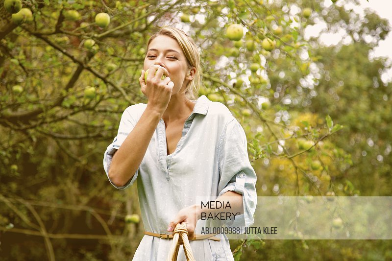 Woman in Orchard Biting Apple