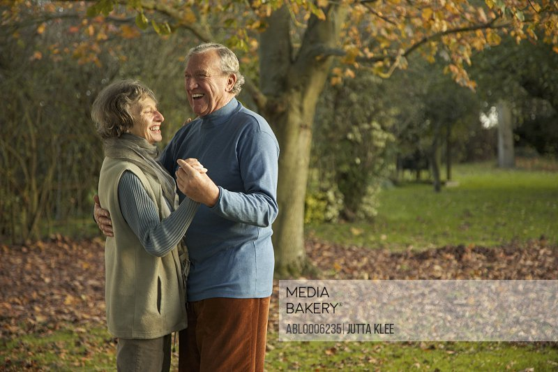 Senior couple dancing in a park