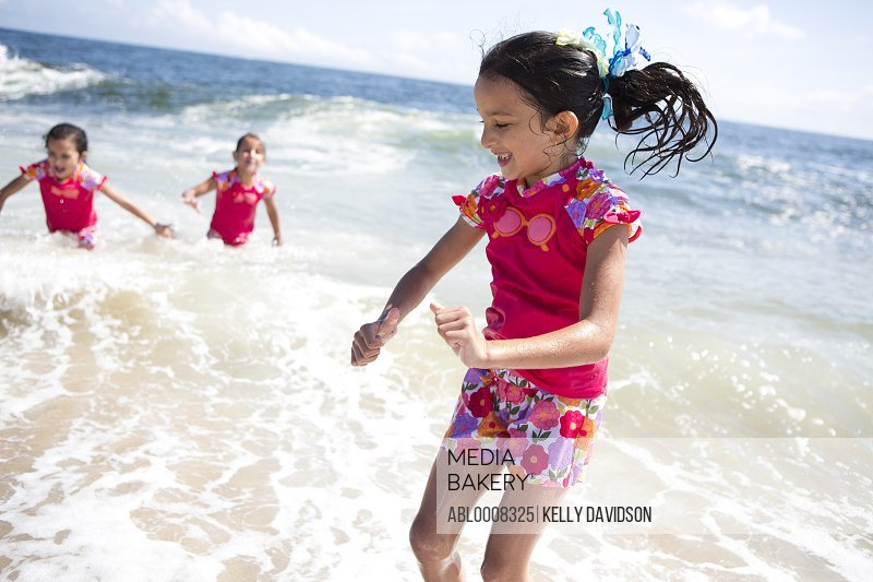 Girls in Matching Outfit Playing in Sea Water