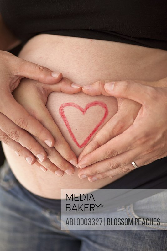 Couple's Hands on Pregnant Stomach with Heart Shape