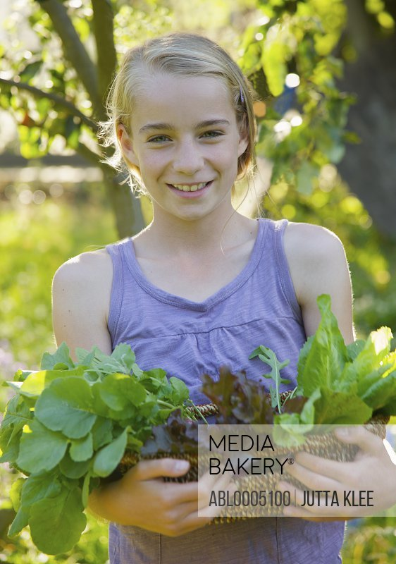 Smiling young girl standing in a garden holding a basket of leafy vegetables