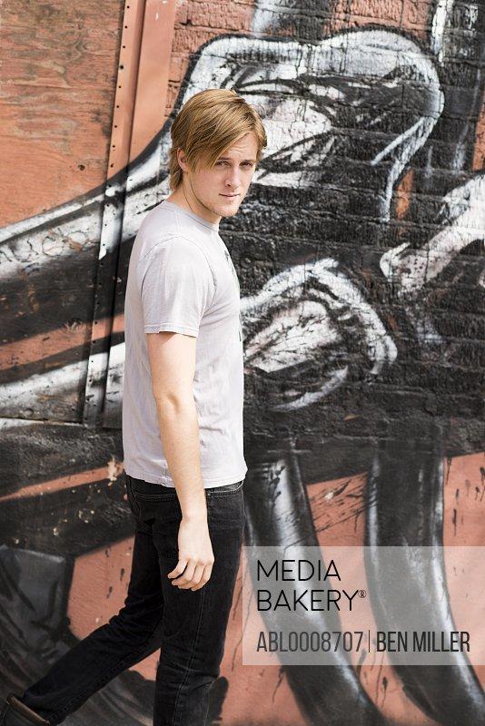 Man Walking by Graffiti Wall