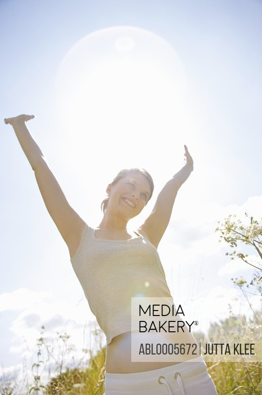 Smiling young woman standing in a field with her arms in air