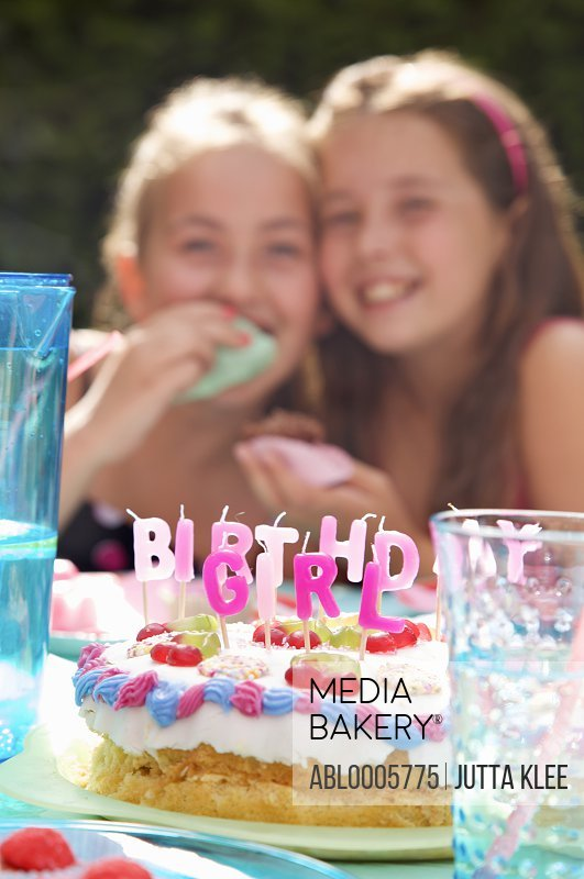 Two smiling young girl sitting behind a birthday cake