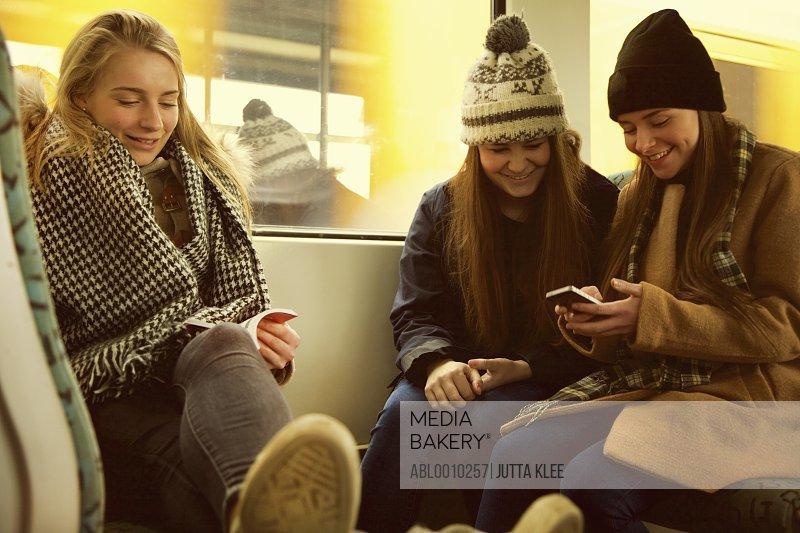 Teenage Girls Sitting on Train Using Smart Phone