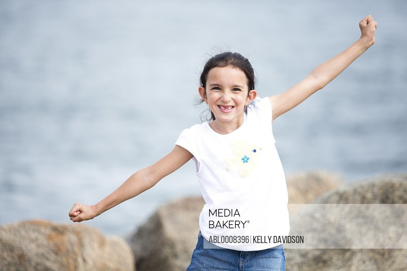 Girl with Arms Outstretched by Sea