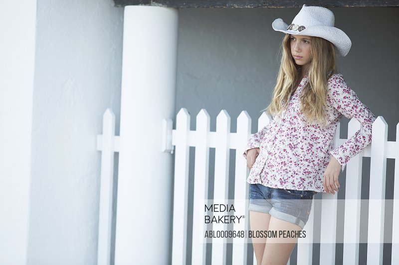 Teenage Girl Wearing Cowboy Hat Leaning on White Picket Fence