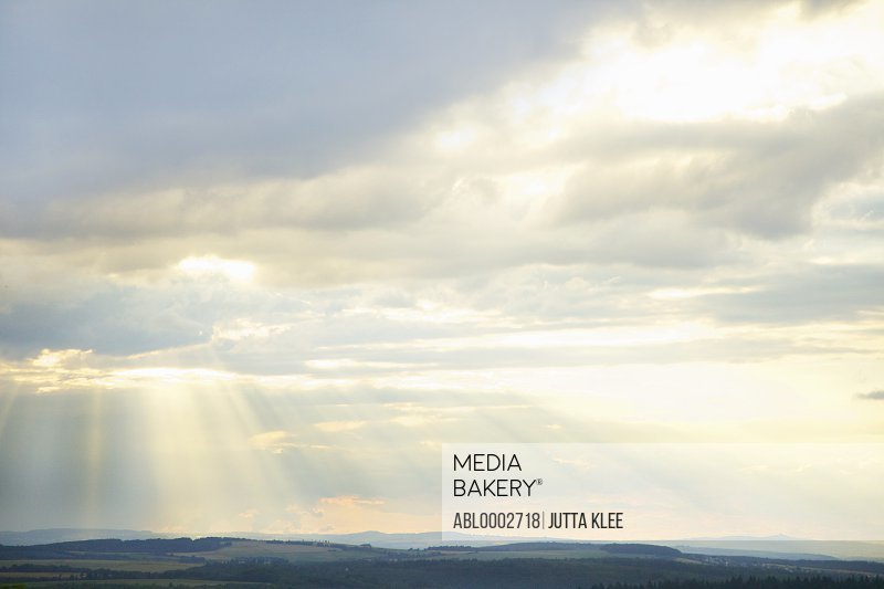 Sunbeams through Clouds over Rural Landscape