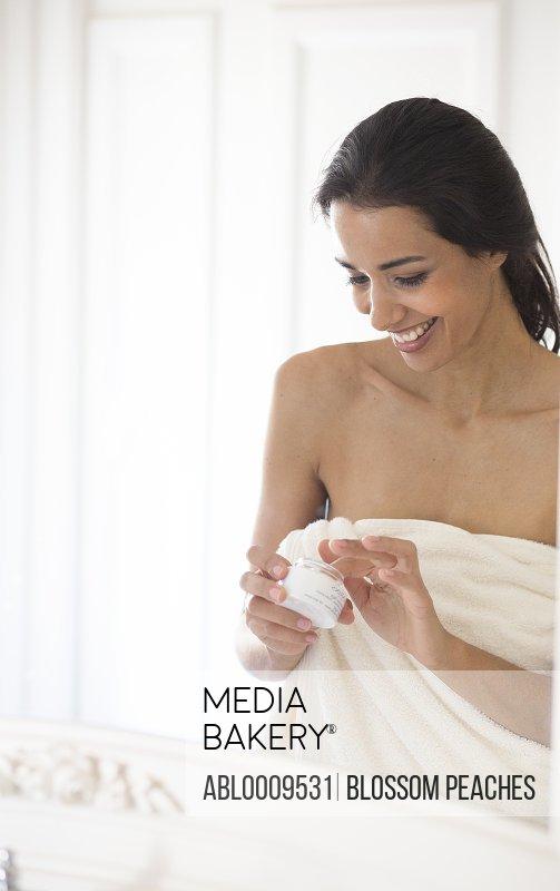 Smiling Woman Applying Moisturizer