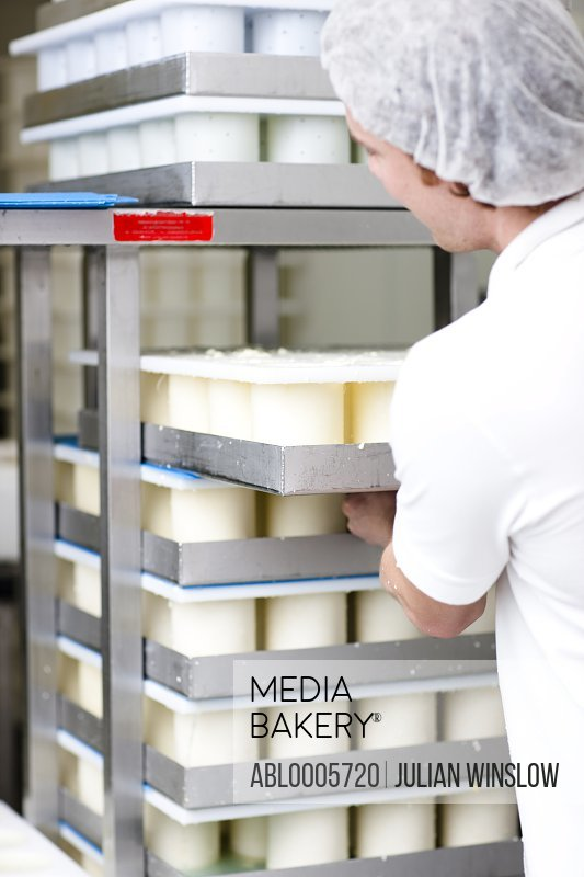 Back view of a man stacking cheese moulds