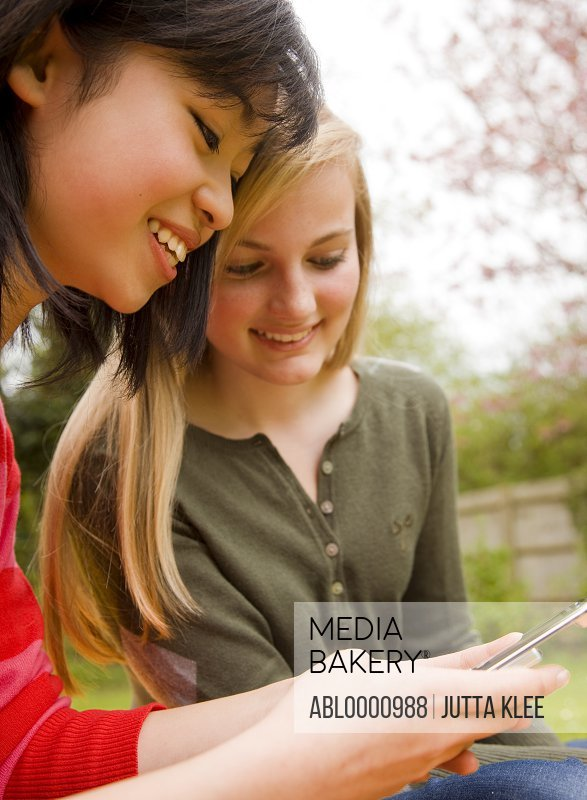 Two smiling teenaged girls  holding and looking at cell phone