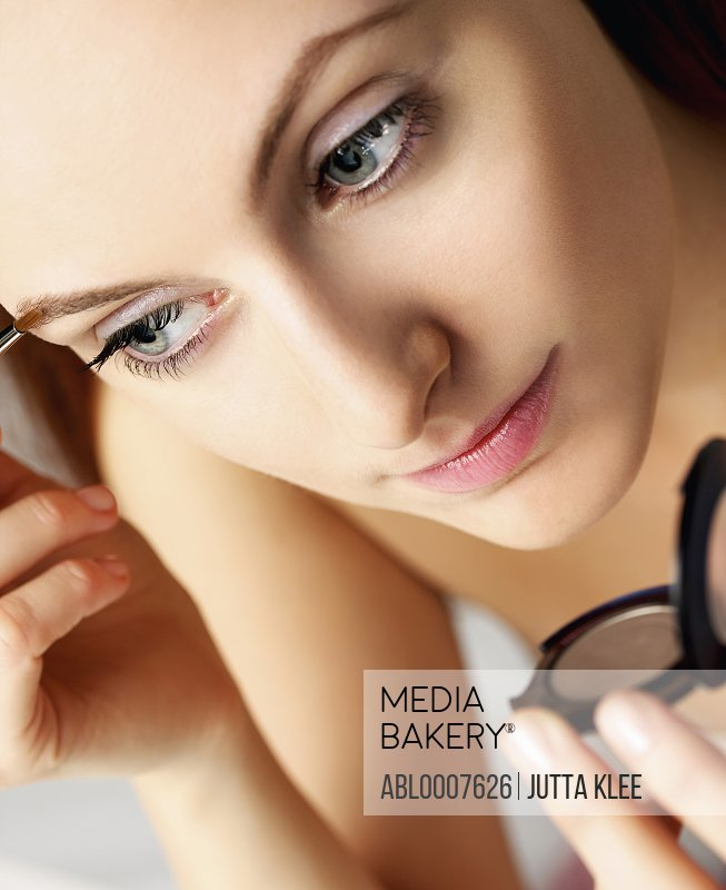 Woman Applying Makeup on Eyebrow