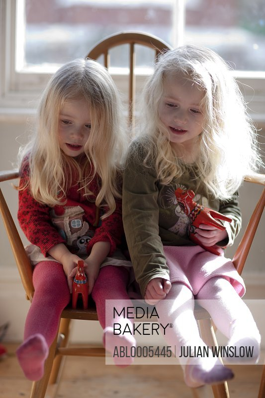 Two girls sitting on the same chair holding toys
