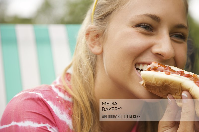 Close up of a teenaged girl eating a hot dog