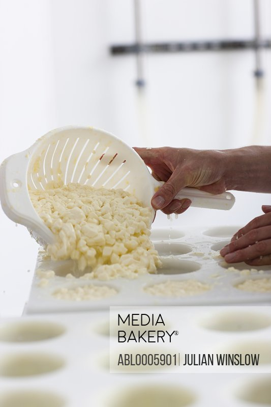 Close up of a man smoothing cheese into moulds