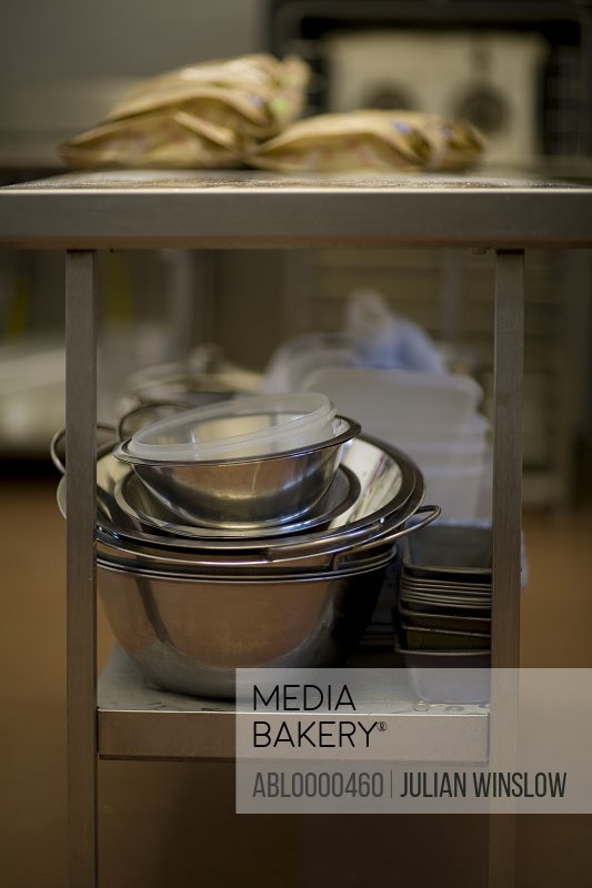 Pile of bowls and tins under square stainless steel kitchen table