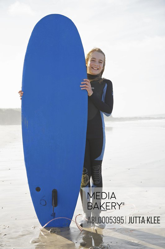Smiling girl holding a surfboard upright