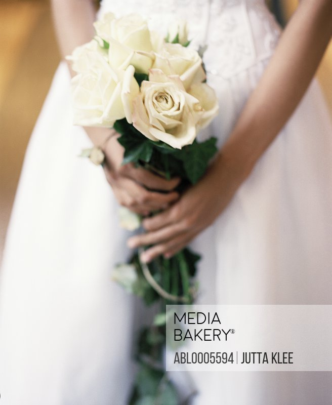 Close up of a bride hands holding a bouquet of white roses