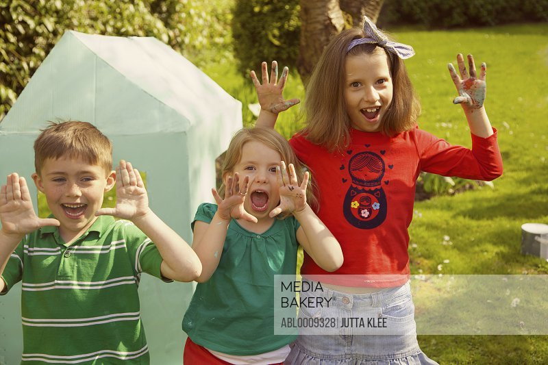 Smiling Children with Hands Raised in Garden