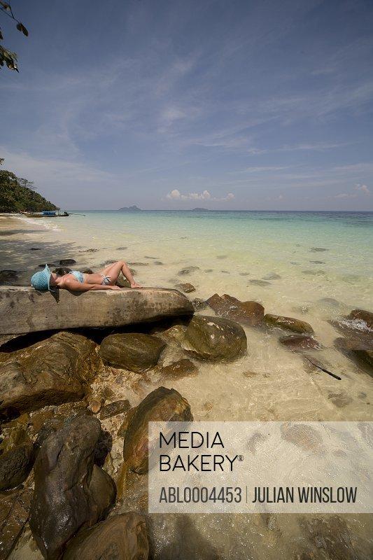 Young woman lying on rocks sunbathing and relaxing