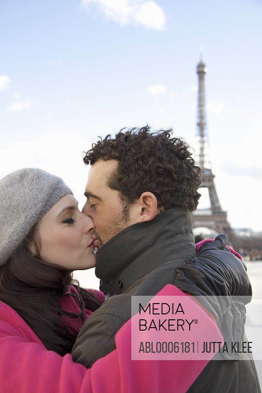 Couple kissing in front of the Eiffel Tower