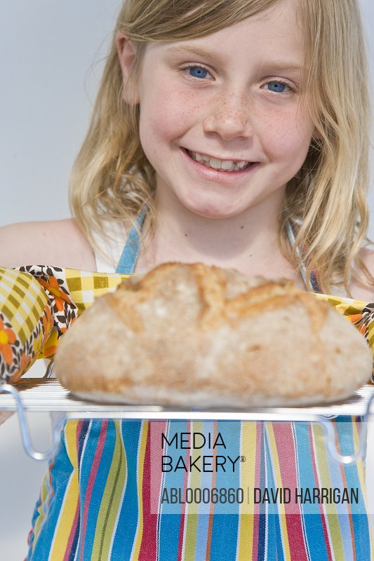 Young Girl Holding Rack with Loaf of Bread