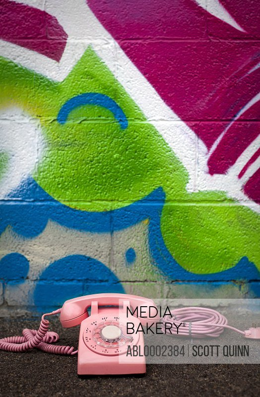 Pink Telephone in front of Graffiti Covered Wall
