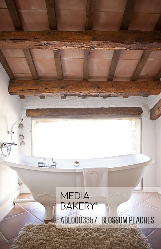 Free Standing Bathtub in Bathroom with Beamed Ceiling