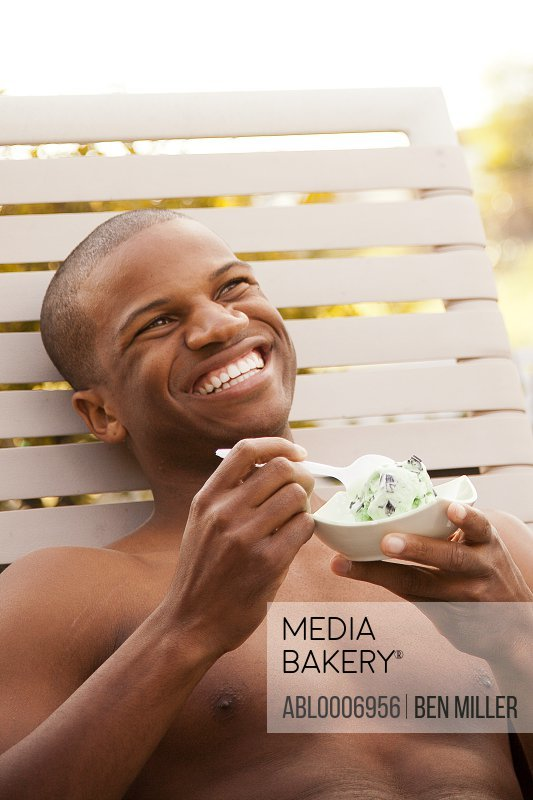 Smiling Bare Chested Man Eating Ice Cream Outdoors