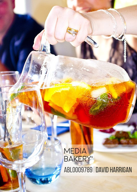 Woman Pouring Pimms Cocktail in Glass