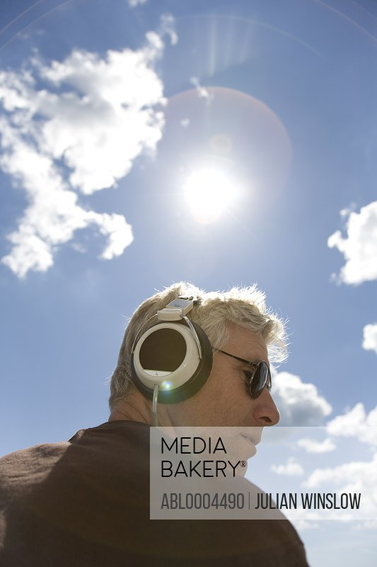 Close up of gray haired man listening to music with headphones against blue sky