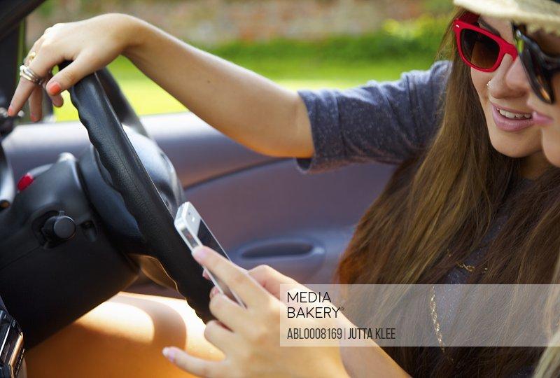 Teenage Girls Using Cell Phone Inside Car