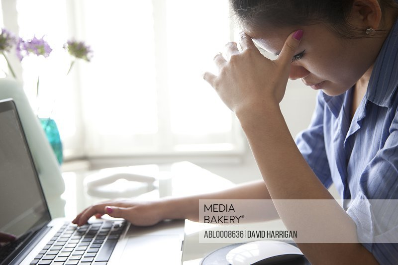 Businesswoman with Hands on Head Using Laptop