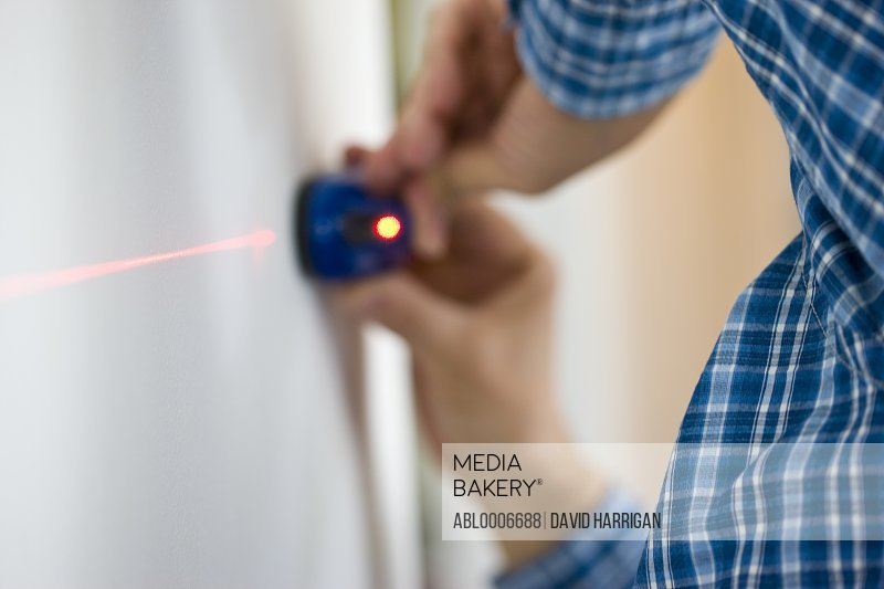 Man's Hands Holding Laser Level against White Wall