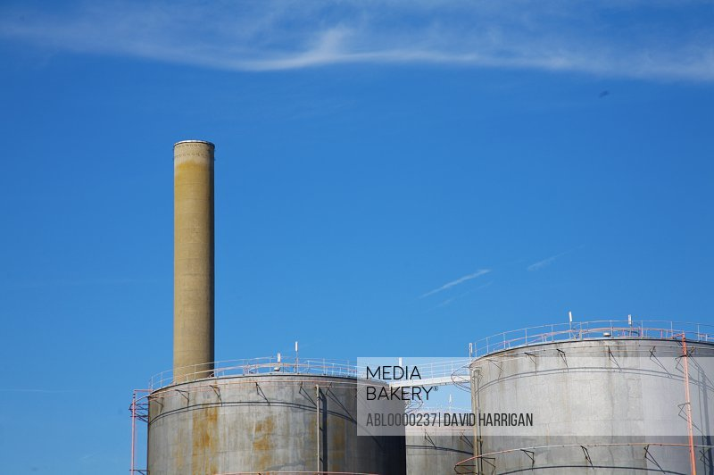 Storage tanks and industrial chimney against blue sky