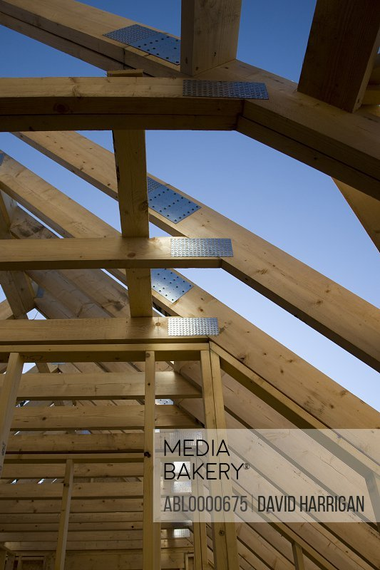 Roof beams of house under construction against blue sky