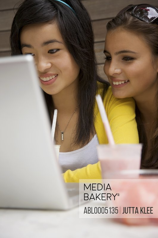 Two smiling teenaged girls sitting in front of laptop computer