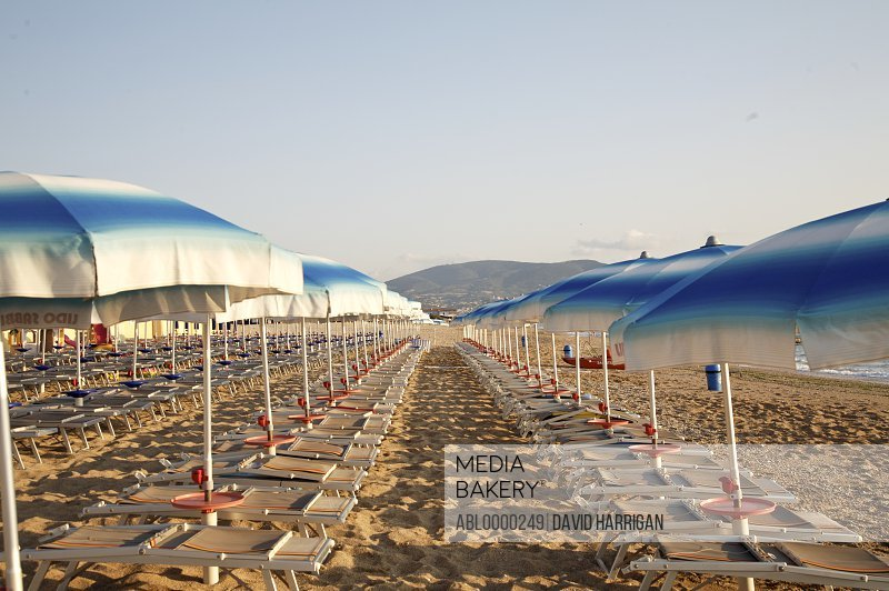Empty beach at sunrise with white and blue parasols and sun loungers
