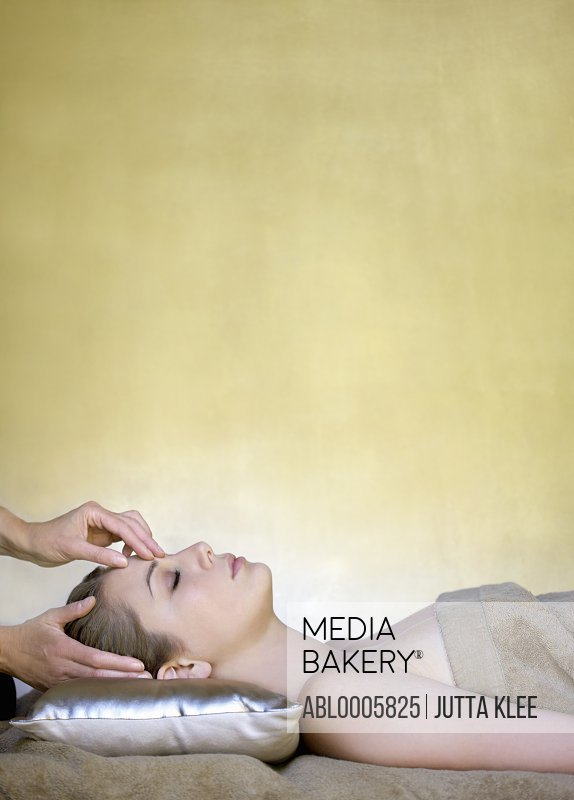 Profile of a young woman receiving a head massage
