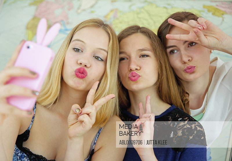 Teenage Girls Taking Selfie whilst Pouting and Making Peace Sign